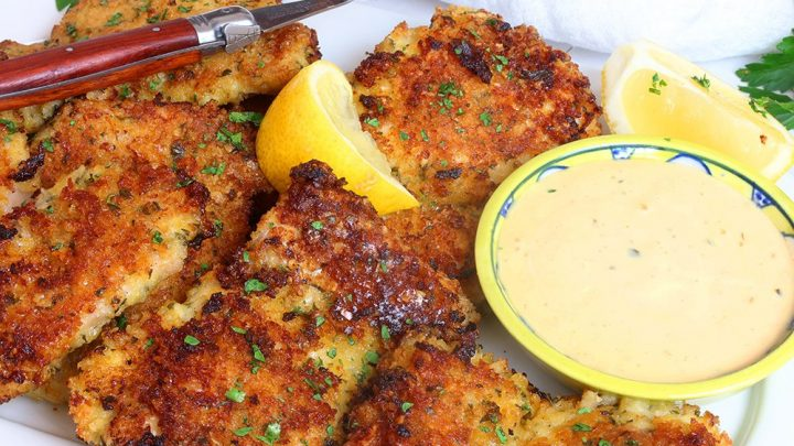 crispy garlic and parmesan panko chicken thighs served on a white plate with wedges of lemons and a sprinling of parsley